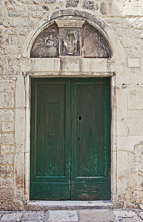 surmounted: Ancient portal with a green wooden door encased in a white stone wall, surmounted by a marble arch with a carved shield; Editorial