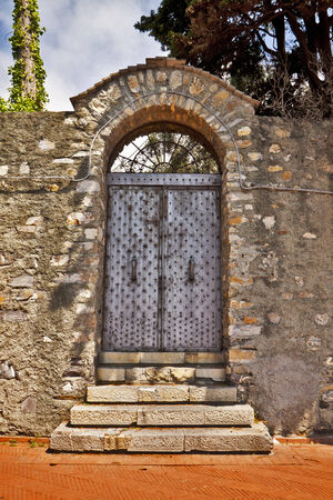 surmounted: Rusty iron door between stone walls surmounted by a stone arch