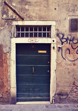 surmounted: Ancient wooden door closed surmounted by a grate with graffiti on wall. Instagram retro effect added