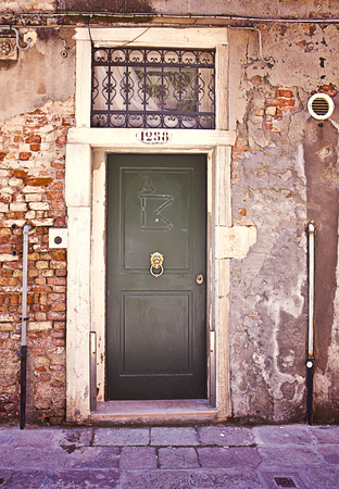 surmounted: Ancient wooden door painted in green surmounted by a grate. Retro effect added