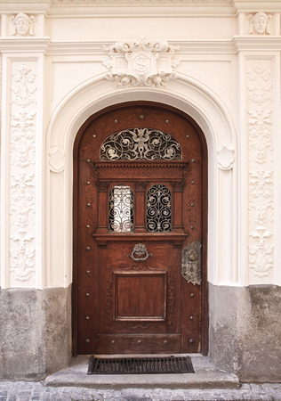 puertas de hierro: Puerta de madera elegante con empu�adura de bronce y decoraciones, enmarcada por columnas de estuco elaborados y arquitrabe