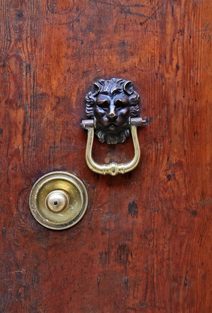 Ancient gate with bossed decoration and lion head shaped door knocker photo