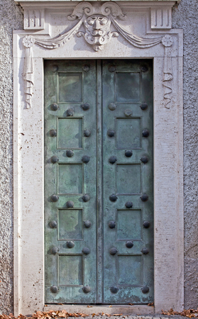 surmounted: Antique bronze portal decorated with shells and surmounted by a marble mask