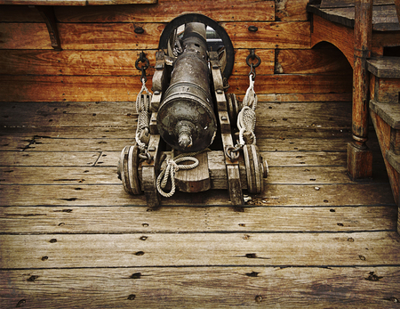 Antique gun ready to fire on antique vessel on grunge texture photo
