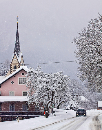 proceeds: Snowfall on Austrian route, a car proceeds carefully on the white route near an idyllic village