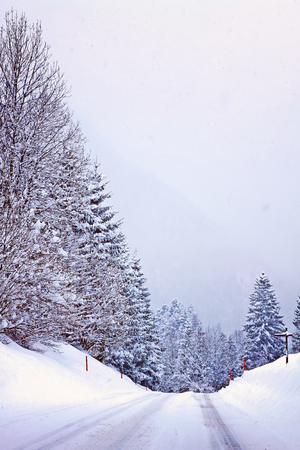 Austrian Alpine route on winter time during snowfall. photo