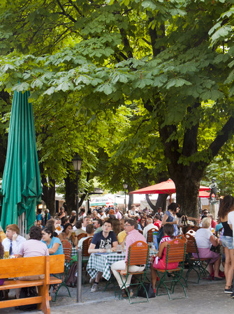 people seat and enjoy beer and food at a open air restaurant at Viktualien Markt in Munich Редакционное