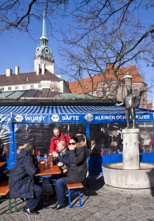 MUNICH, GERMANY: people seat and drink beer open air at Viktualien Markt in Munich in a sunny  winter day.