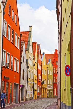 landshut: LANDSHUT, GERMANY - view of a narrow cobbled street in  Landshut center, Bavarian medieval town near Munich. Landshut was founded on 1204, the facades of its buildings maintain a characteristic Renaissance style and  bold colors