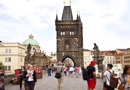 lasted: Tourists cross the Charles Bridge over the Moldau  river to the Old Town of Prague.The bridge construction begun on 1357 and lasted 70 years.