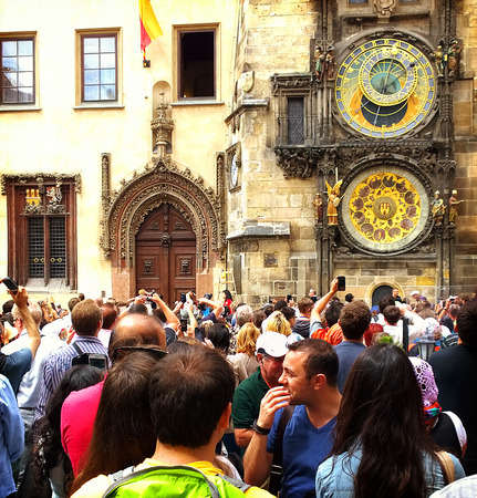unesco in czech republic: Tourists visit and take pictures of the astronomical clock in Prague. The clock was first installed in 1410, making it the third-oldest astronomical clock in the world and the oldest one still working.