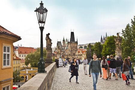 lasted: Tourists cross the Charles Bridge, linking over the Moldau river the Prague Castle with the Old Town.The bridge construction begun on 1357 and lasted 70 years.