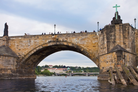 unesco in czech republic: PRAGUE, CZECH REPUBLIC  Tourists admire the view of the Moldau river and the city from the Charles Bridge, medieval construction linking the Old Town with the Castle of Prague Editorial