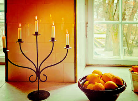 candle holder: Still life, basket with oranges near a window and lit candles on iron candle holder.