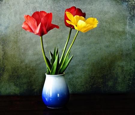 Interior, three tulips red and yellow in vase on grunge dark background