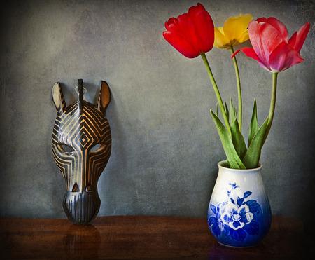 Vintage still life, three tulips in vase and wooden african mask