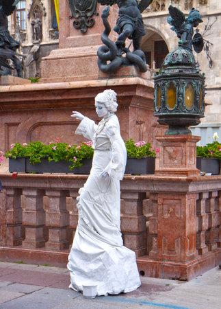 pretender: Munich, Germany - street artist painted in white performs in central Marienplatz Editorial