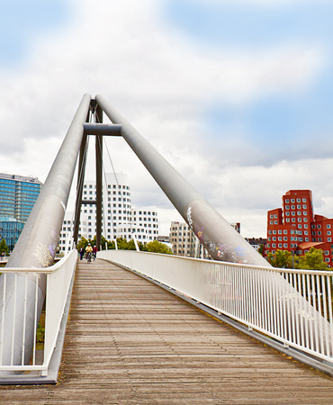 static bike: Dusseldorf, Germany - pedestrian bridge on Rhine river with the view of the Neuer Zollhof,  landmark of Media Harbor, with the leaning towers Editorial
