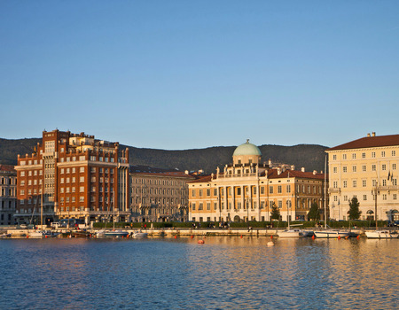 rive: Trieste Italy - city waterfront (Le Rive) on sunset with the view of neo-classical facade of Carciotti Palace, first headquarter of Generali Insurance