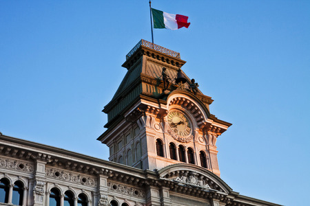 surmounted: Trieste, Italy - Unity of Italy Square, architectural detail of City Hall  tower surmounted by Italian flag, view of  clock, quarter bell with bronze figure at sunset