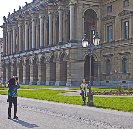 residenz: Munich, Germany - Asian tourist takes a souvenir picture of a friend in front of Residenz, former city residence of the Bavarian kings. Editorial