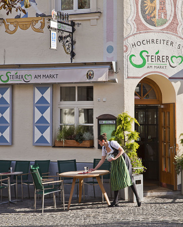 restaurant tables: Munich, Germany - waitress cleans and prepares tables outside a popular brewery in Munich city center