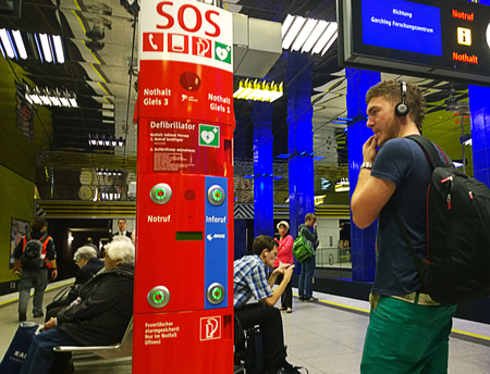 subway station: Munich, Germany - student reading the safety information at the SOS point at Muenchner Freiheit subway station
