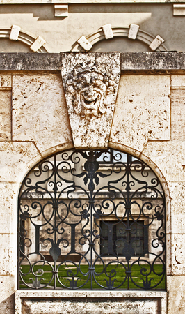 surmounted: antique stone wall with window closed by artistic iron grille surmounted by a carved laughing mask Stock Photo