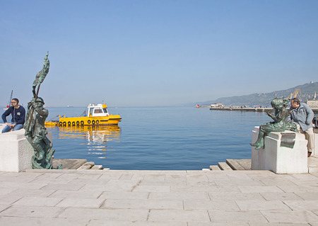 infantryman: Trieste, Italy - waterfront sea promenade Le Rive with an antipollution boat crossing by.Pier with bronze monuments to the side of the landing stage, an Italian infantryman bersagliere to the left and two Trieste girls to the right.