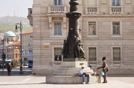 ambulant: Trieste, Italy  - Unity of Italy Square, two black ambulant vendors rest near a bronze pillar on a sunny day Editorial
