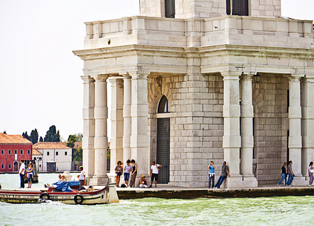 keystone light: Venice, Italy - view of Punta della Dogana at the confluence of Grand Canal with Giudecca Canal, motor boat passing by and tourists relaxxing and resting in the shadow of Dogana palace, the old Custom House of Venice.