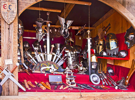 traditional weapon: Munich, Germany - medieval stall at traditional Medieval Christmas market  Mittelaltermarkt at Wittelsbacher Platz in Munich.On sell knives, many kind of cutting weapon, helms  and armor pieces