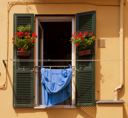 red shutters: Italian colors: window with open shutters, red geranium vases and bue laundry hanging in the sun Stock Photo