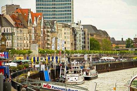 in the open air: DUSSELDORF, GERMANY - Rhine waterfront, antique and modern buildings, alley with trees and street lamps, open air restaurants and touristic cuise ships Editorial