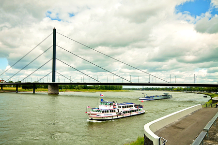 ewer: DUSSELDORF, GERMANY -view of Rhine river from Dusseldorf waterfront with touristic cruise boat, ewer and bridge Editorial
