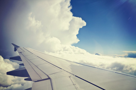 View from airplane, carrier wing and beautiful cumulus of white clouds against blue sky, grunge effect added.