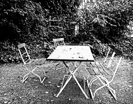 melancholia: garden corner in autumnal mood,empty chairs and table with fallen leaves