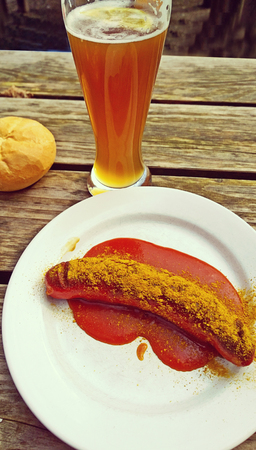wurst: Bavarian beer garden food, curry wurst with bread and beer on grunge wooden table