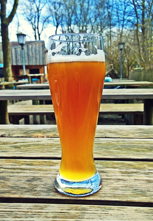 drink responsibly: Traditional wheat beer at Bavarian beer garden, blurred background