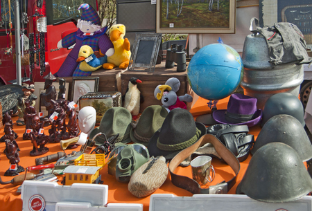 plush toys: Various stuff on display at open air spring flea market, helmets, globe, plush toys, carved figurines, frames, gas mask