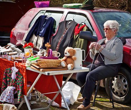 used clothes: Seller at open air flea market knits while awaiting customers seated at her market stall