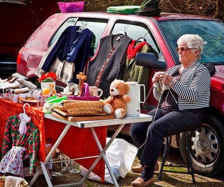 Verkäufer bei Open-Air-Flohmarkt strickt, während warten auf Kunden an ihrem Marktstand sitzt Standard-Bild - 56161267