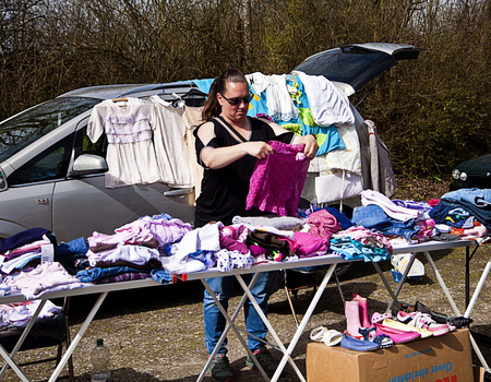used clothes: Seller displays her wardrobe merchandise on her market stall at flea market