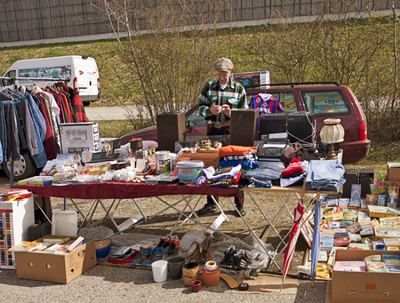 used clothes: Eching, Germany - seller at spring open air flea market; on display books, used clothes, home appliance and tools Editorial
