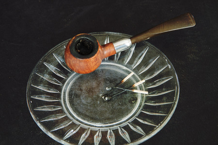 Used and worn smoking pipe on glass ashtray with burned matches