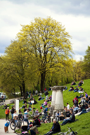 leisurely: Munich, Germany - people in a festive day of spring sitting leisurely on green lawn and stairs at Bavaria park with the view of flowering trees Editorial