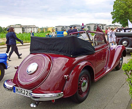 GARCHING, GERMANY - Vintage cars at the traditional parade in Bavarian town Garching near Munich: rear view of a red shiny old IFA cabriolet, produced in GDR in the years 1949-1956