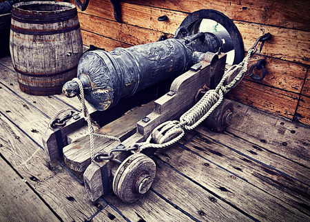 deck cannon: Antique gun ready to fire on antique vessel. Grunge texture added