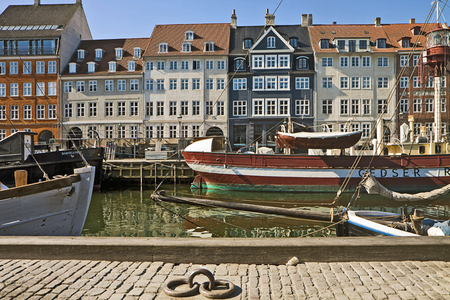 flanked: Panoramic view of Nyhavn, famous touristic landmark of Copenhagen, waterfront  built in 17th-century flanked by antique houses with bright colorful facades and harbor for old ships. Editorial