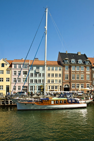 flanked: Pictorial view of Nyhavn, famous touristic landmark of Copenhagen and waterfront built in 17th-century flanked by antique houses with bright colorful facades.